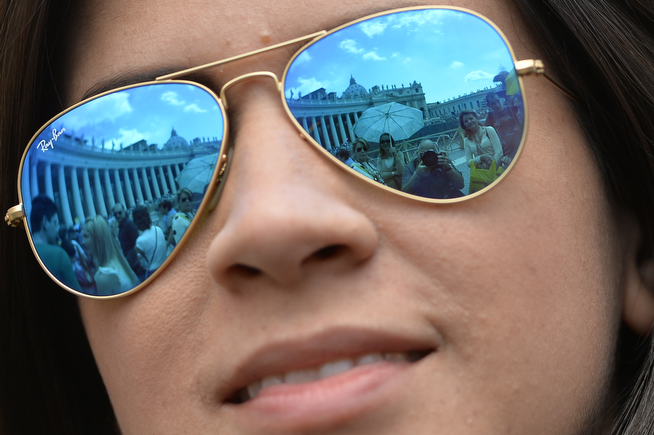 . St Peter\'s square is reflected in the glasses of a woman on April 26, 2014 at the Vatican a day before the canonisation of Popes John XXIII and John Paul II. Popes John Paul II and John XXIII will join the roster of saints at a historic Vatican ceremony on Sunday seen as an attempt to unite conservatives and reformists, with some 800,000 pilgrims expected in Rome. The double canonisation of two of modern-day Catholicism\'s most influential figures will be presided over by Pope Francis and may be attended by his elderly predecessor Benedict XVI, bringing two living pontiffs together to celebrate two deceased predecessors.  (ANDREAS SOLARO/AFP/Getty Images)
