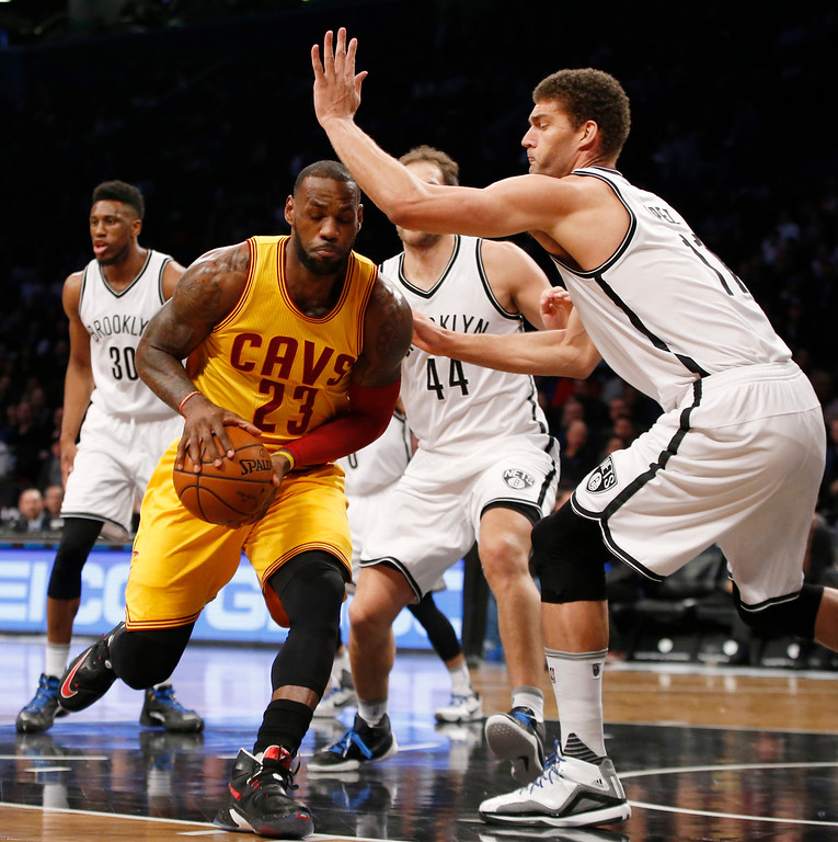 . Brooklyn Nets center Brook Lopez (11) defends Cleveland Cavaliers forward LeBron James (23) who drives to the basket in the paint in the first half of an NBA basketball game, Thursday, March 24, 2016, in New York. (AP Photo/Kathy Willens)