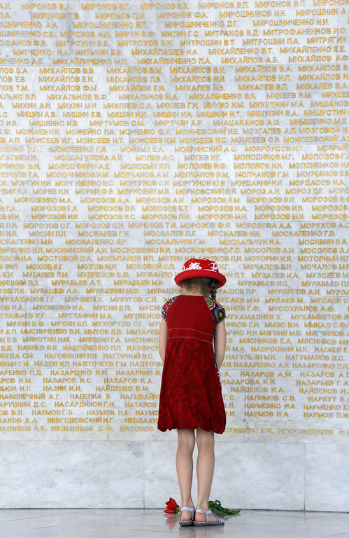 . A girl lays a floral tribute at the Remembrance Wall of the Soviet Union Heroes during the anniversary of victory over the Nazis, in Ukraine\'s capital Kiev, Thursday, May 9, 2013. Ukrainians continue to celebrate the World War II anniversary and Victory Day on May 9 as a national holiday. (AP Photo/Efrem Lukatsky)