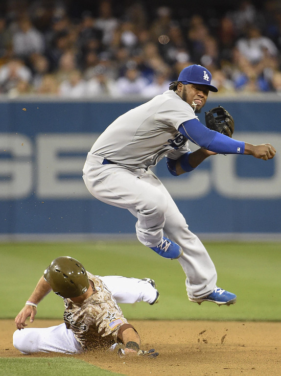 . Hanley Ramirez #13 of the Los Angeles Dodgers jumps over Tommy Mendica #14 of the San Diego Padres as he turns a double play during the seventh inning of a baseball game on Opening Night at Petco Park on March 30, 2014 in San Diego, California.  (Photo by Denis Poroy/Getty Images)