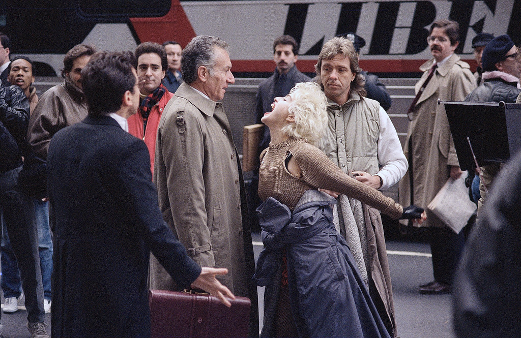 """. Madonna reacts for the camera during the filming of the movie \""""Slammer\"""" on Fifth Avenue while her co-star, Griffin Dunne, looks over her shoulder in New York, Nov. 12, 1986. In the romantic comedy, Madonna plays a paroled thief who, with her lawyer, Dunne, searches for the real criminal. (AP Photo/Richard Drew)"""