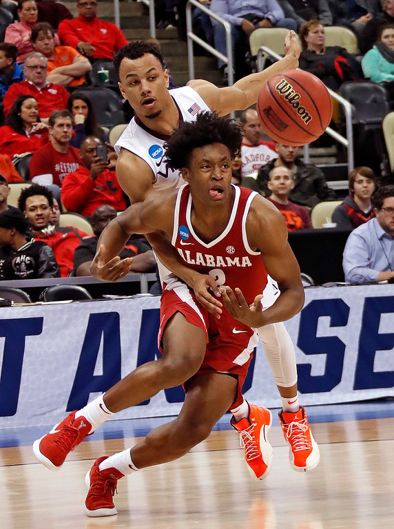 . Virginia Tech\'s Justin Robinson, rear, knocks the ball away from Alabama \'s Collin Sexton (2) during the first half of an NCAA men\'s college basketball tournament first-round game, in Pittsburgh, Thursday, March 15, 2018. (AP Photo/Gene J. Puskar)