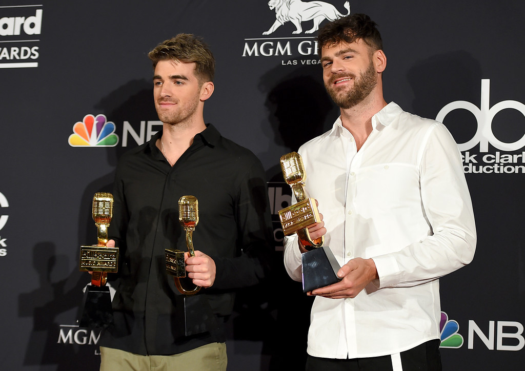 """. Andrew Taggart, left, and Alex Pall of \""""The Chainsmokers\"""" pose in the press room with the awards for top dance/electronic artist, top dance/electronic song for \""""Something Just Like This\"""" and top dance/electronic album \""""Memories�Do Not Open\"""" at the Billboard Music Awards at the MGM Grand Garden Arena on Sunday, May 20, 2018, in Las Vegas. (Photo by Jordan Strauss/Invision/AP)"""