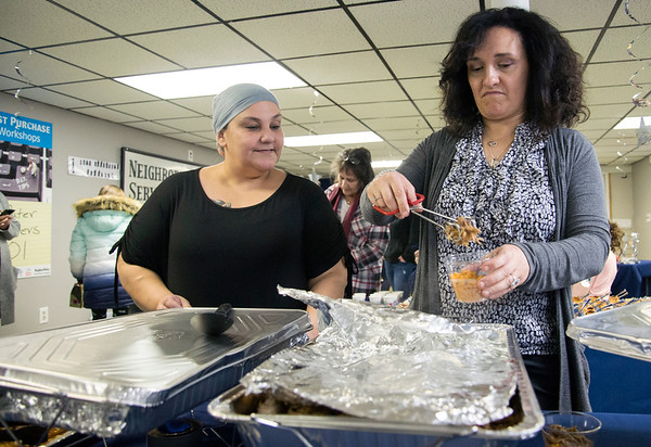 01/06/19 Wesley Bunnell | StaffrrThree Kings Day was celebrated at Neighborhood Services of New Britain at 223 Broad St for families on Monday night. Idalis Moreno, L, and Maria Rosiello put together cups of food for guests.