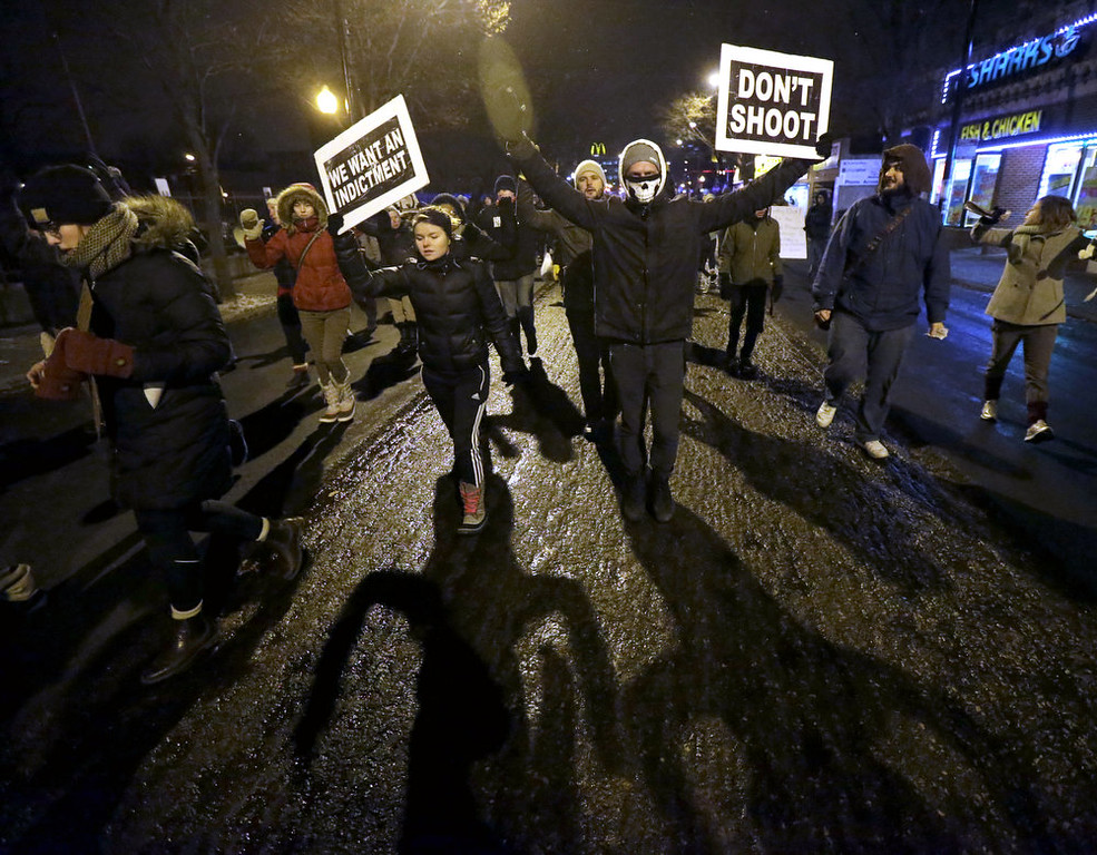 . Protesters march during a rally near the Chicago Police headquarters after the announcement of the grand jury decision not to indict police officer Darren Wilson in the fatal shooting of Michael Brown, an unarmed black 18-year old, Monday, Nov. 24, 2014, in Chicago. (AP Photo/Charles Rex Arbogast)