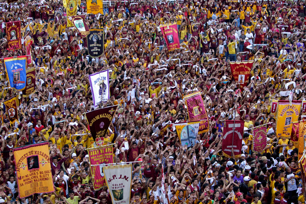 . Devotees raise their hands in prayer during the start of the annual procession of the Feast of the Black Nazarene in Manila January 9, 2013. The Black Nazarene, a life-size wooden statue of Jesus Christ carved in Mexico and brought to the Philippines in the 17th century, is believed to have healing powers in the predominantly Roman Catholic country. It is paraded through the narrow streets of Manila\'s old city from dawn to midnight. Police said about 500,000 people joined the procession on Wednesday.  REUTERS/Erik De Castro