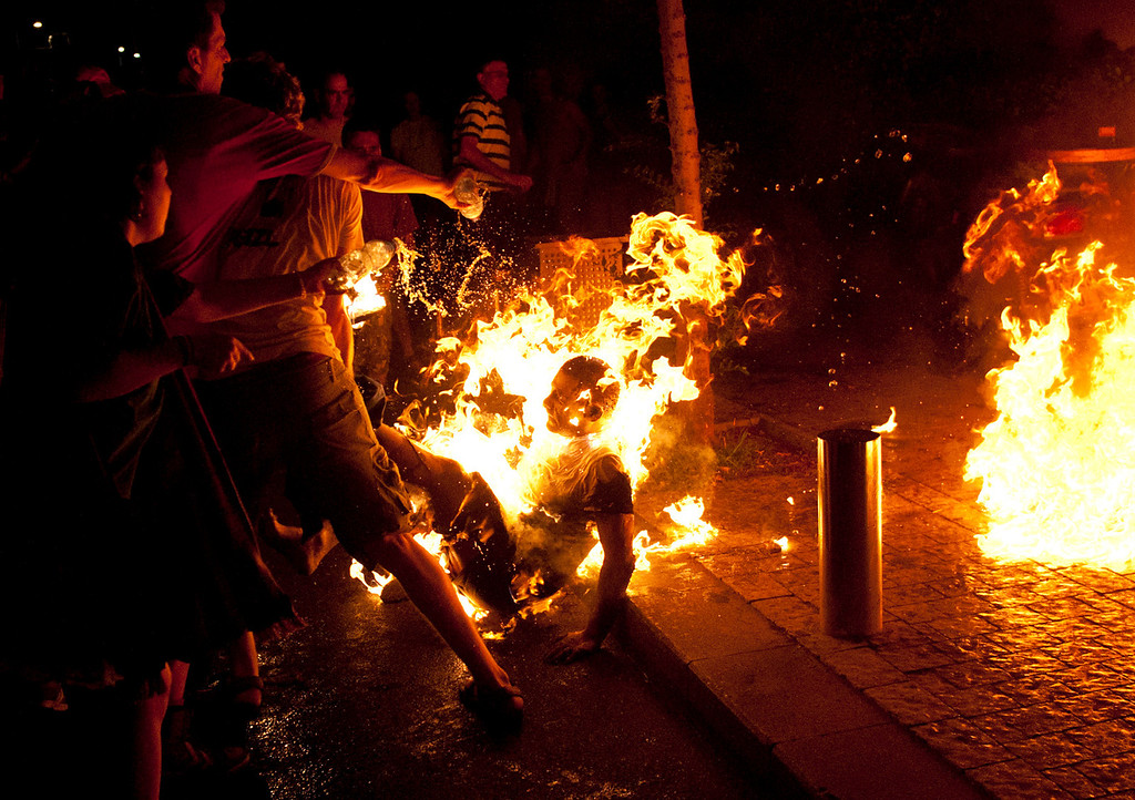 . In this July 14, 2012 file photo, people try to extinguish the fire after a man set himself alight in Tel Aviv, Israel during rally marking the anniversary of a wave of demonstrations that swept the country to protest the high cost of living and other social issues. He was later rushed to a hospital where he was being treated for serious burns, police said.  (AP Photo/Ben Kelmer, File)