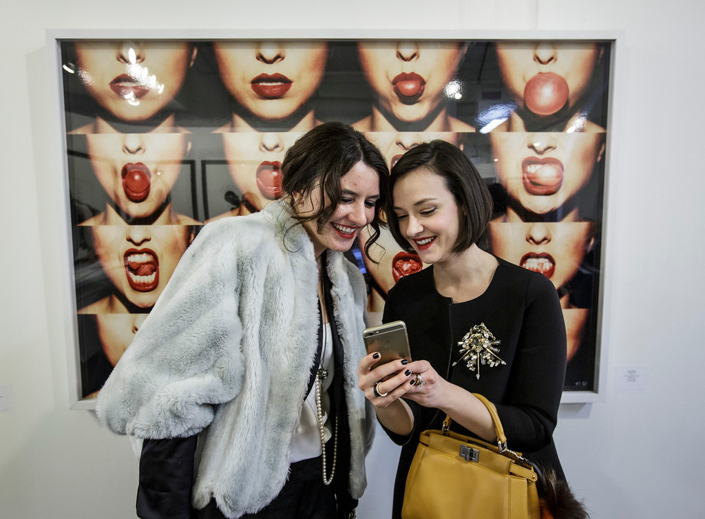 """. Coxy Rodoni, left, and Marta Gastini view a photo shot of them in front of \""""Bubble Gum\"""" a photo by Tyler Shields at the photo la opening party held at The REEF/LA Mart in Los Angeles, CA. January 15, 2015.  Photo by David Sprague/Special to the Daily News"""