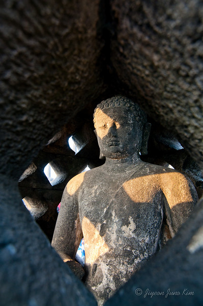 Buddha statue inside of the stupa at Borobudur temple