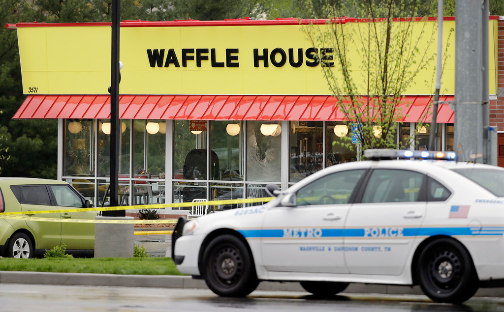 . A police car sits in front of a Waffle House restaurant Sunday, April 22, 2018, in Nashville, Tenn. At least four people died after a gunman opened fire at the restaurant early Sunday. (AP Photo/Mark Humphrey)