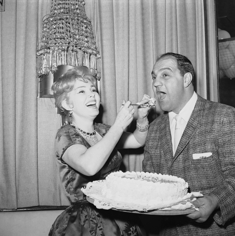 . Zsa Zsa Gabor gives some of her cake to Rocky Marciano, former world heavyweight boxing champ at birthday party for the Actress on Feb. 5, 1961 in New York. Hollywood and Broadway stars attended the party held at the stork club.   (AP Photo/Marty Lederhandler)