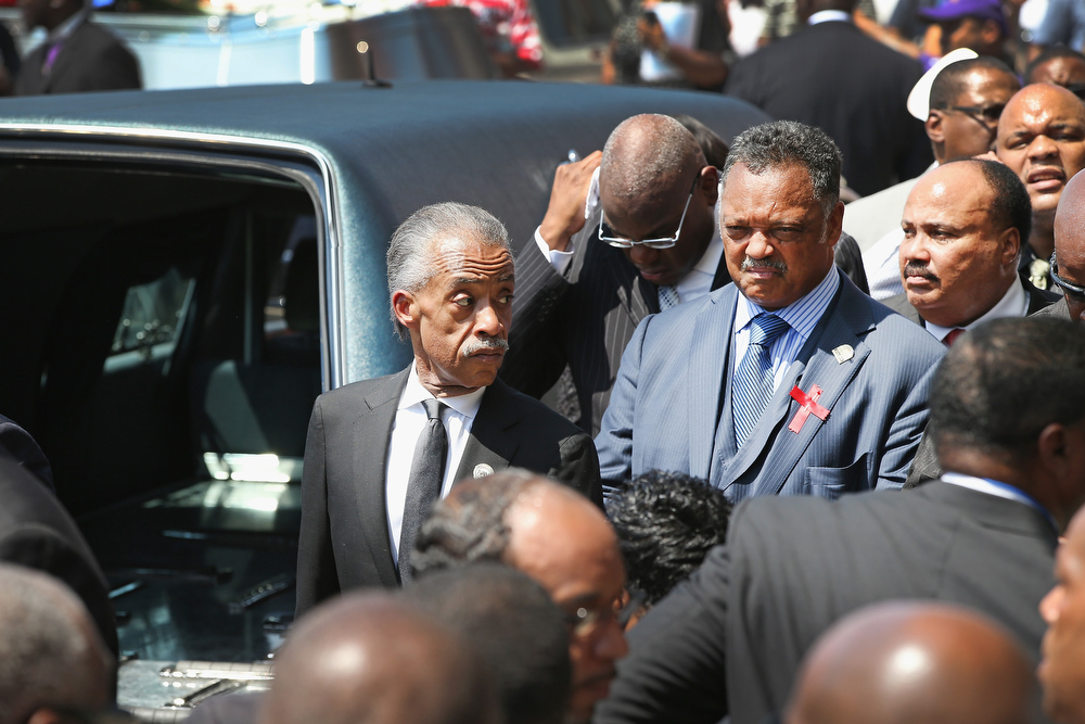 Description of . Civil rights leaders Rev. Al Sharpton (L) an Rev. Jesse Jackson wait for the remains of Michael Brown to be loaded into a hearse following his funeral services at the Friendly Temple Missionary Baptist Church on August 25, 2014 in St. Louis, Missouri. Michael Brown, an 18 year-old unarmed teenager, was shot and killed by Ferguson Police Officer Darren Wilson in the nearby town of Ferguson, Missouri on August 9. His death caused several days of violent protests along with rioting and looting in Ferguson.  (Photo by Scott Olson/Getty Images)