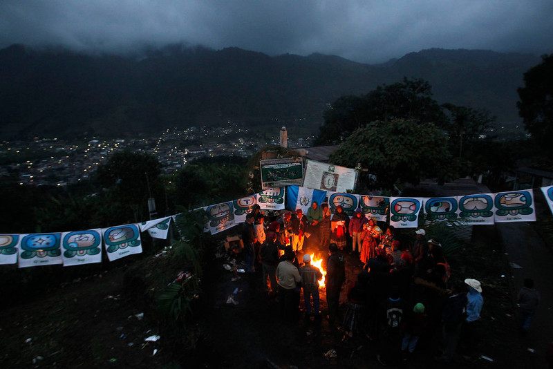 ". People pray around a sacred fire during the pre-Hispanic mass of ""The welcome of the Grandfather Sun and of the Sacred New Fire to the Humanity\"", to receive the 13th Baktun, in the morning, outside the Chi Ixim church in Tactic, Alta Verapaz region, Guatemala, December 21, 2012. This week, at sunrise on Friday, December 21, an era closes in the Maya Long Count calendar, an event that has been likened by different groups to the end of days, the start of a new, more spiritual age or a good reason to hang out at old Maya temples across Mexico and Central America. The Chi Ixim church is a sacred Mayan site. REUTERS/Jorge Dan Lopez"