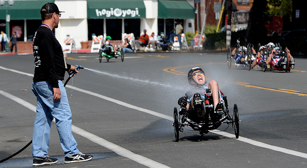 """. Greg Johnson of Loma Linda sprays down cyclists in PossAbilities Paracycle Criterium Sunday April 7, 2013 during the Redlands Bicycle Classic. Johnson who suffered a spinal chord injury nearly 30 years ago says he offers to spray down the cyclists because \""""some of these guys have lost the ability to sweat.\"""" Crowds of spectators gather along the streets of Redlands for the final day of the 29th Annual Redlands Bicycle Classic. Rick Sforza/Staff photographer"""