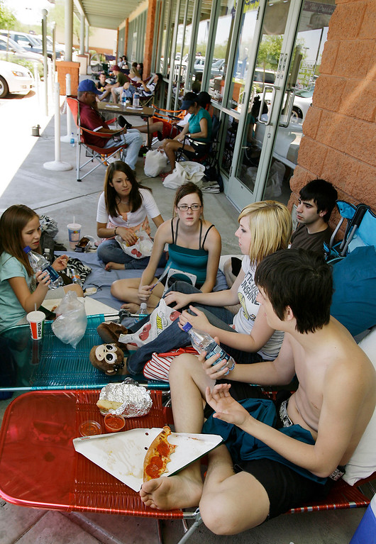 . A group of thirty people lined up in front of an AT&T phone store waiting outside in the 110-degree heat to buy the new Apple iPhone, Friday, June 29, 2007 in Glendale, Ariz.  Tom Bogardus, 17, right, of Surprise, Ariz., eats lunch with friends as they waited for 6 p.m. and the sales release of the new iPhone.  (AP Photo/Ross D. Franklin)