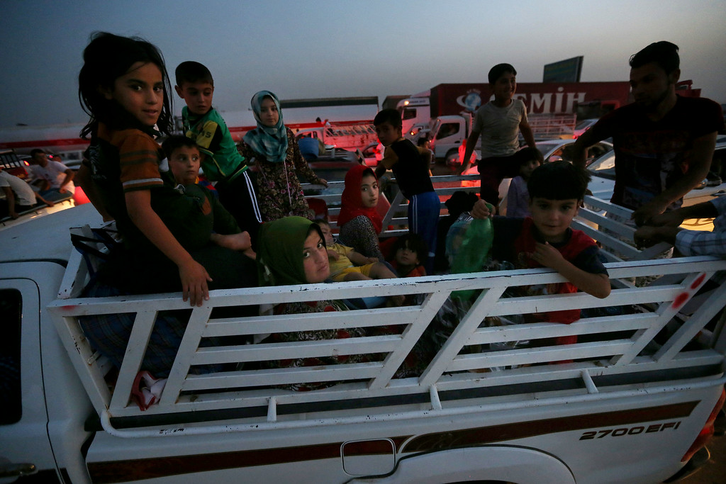 . Fleeing Iraqi citizens from Mosul and other northern towns sit in a pick up truck waiting to cross, in the Khazer area between the Iraqi city of Mosul and the Kurdish city of Irbil, northern Iraq, Wednesday June 25, 2014.  (AP Photo/Hussein Malla)