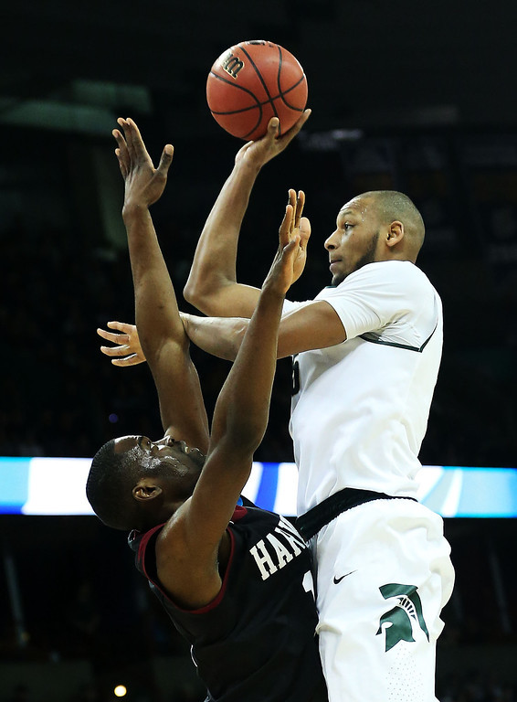 . SPOKANE, WA - MARCH 22:  Adreian Payne #5 of the Michigan State Spartans shoots over Siyani Chambers #1 of the Harvard Crimson in the second half during the Third Round of the 2014 NCAA Basketball Tournament at Spokane Veterans Memorial Arena on March 22, 2014 in Spokane, Washington.  (Photo by Stephen Dunn/Getty Images)