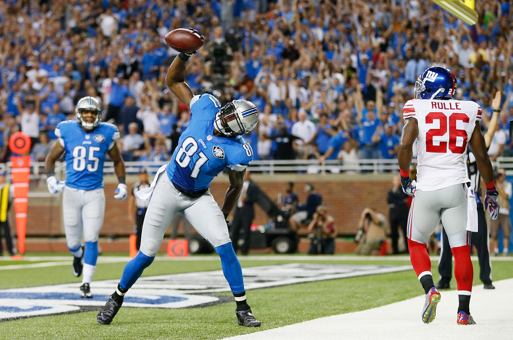 . Detroit Lions wide receiver Calvin Johnson throws down the football after scoring on a 16-yard reception during the first quarter of an NFL football game against the New York Giants in Detroit, Monday, Sept. 8, 2014. (AP Photo/Rick Osentoski)