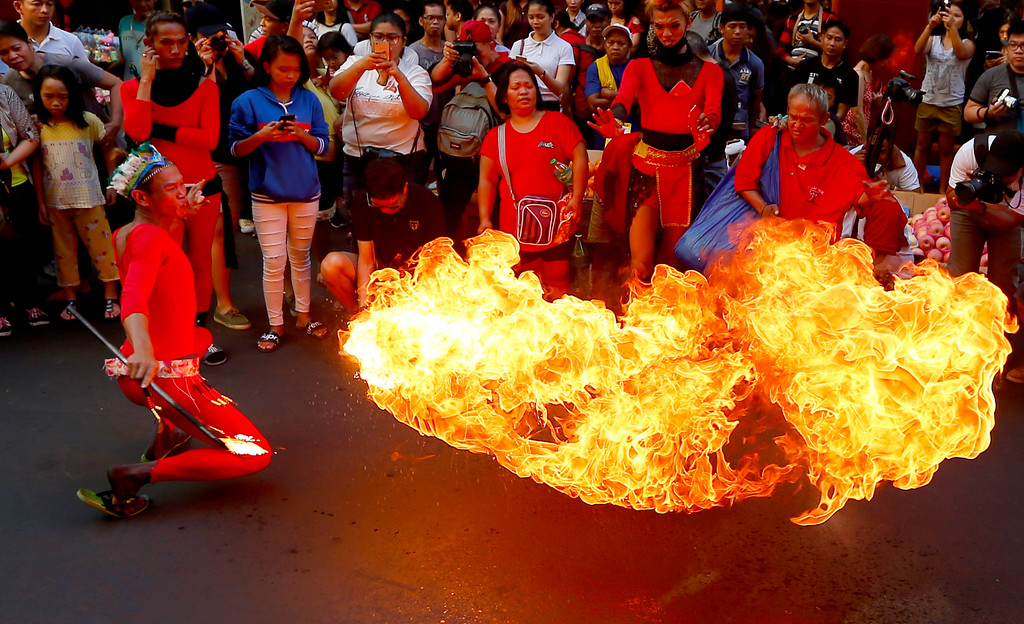 . A fire-eater performs on the street in celebration of the Chinese Lunar New Year Friday, Feb. 16, 2018 at Manila\'s Chinatown district, Philippines. This year is the Year of the Dog in the Chinese Lunar calendar. (AP Photo/Bullit Marquez)