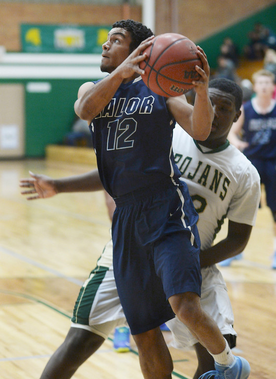 . Valor\'s Marcus Wilson (12) worked the baseline in front of Trojans\' defender Levi Watson (22) in the first half. The Valor Christian High School boy\'s basketball team defeated Aurora Central 60-52 Wednesday night, January 8, 2014. Photo By Karl Gehring/The Denver Post