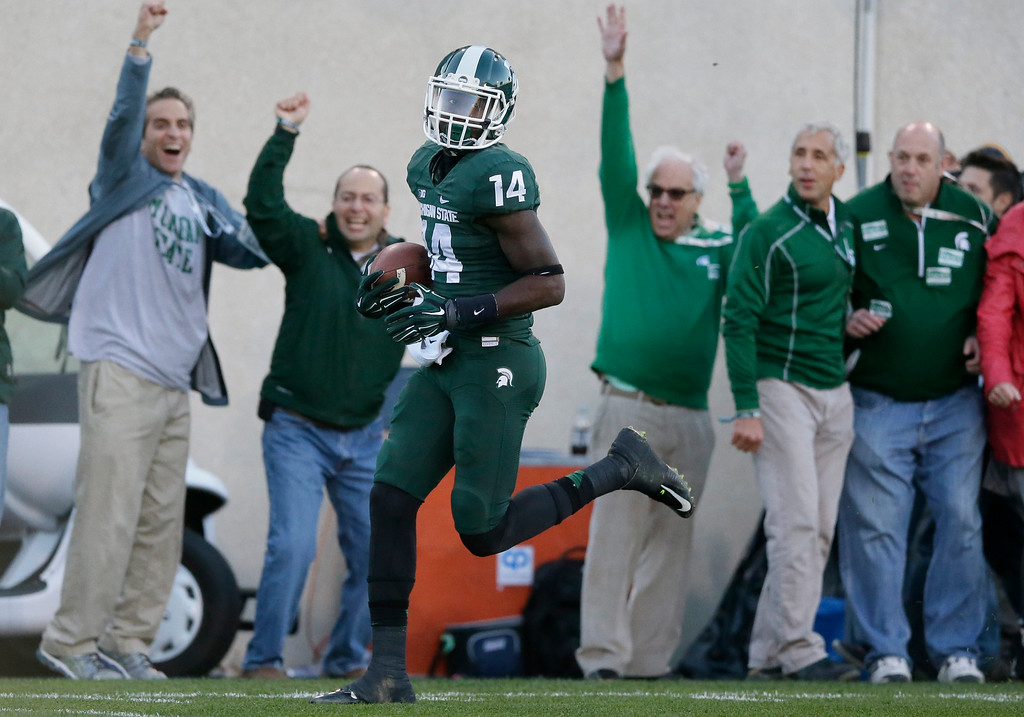 . Michigan State wide receiver Tony Lippett (14) scores a 70-yard touchdown during the second half of an NCAA college football game against Michigan in East Lansing, Mich., Saturday, Oct. 25, 2014. (AP Photo/Carlos Osorio)