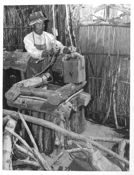 """""""George S. Takemura, landscape artist from West Los Angeles, builds a rustic wishing well at Manzanar, a War Relocation Authority center where evacuees of Japanese ancestry will spend the duration.""""--caption on photograph"""