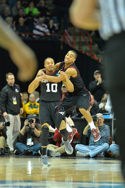 March 20, 2014: Harvard Crimson guard Siyani Chambers (1) and Harvard Crimson guard Brandyn Curry (10) celebrate after upsetting Cincinnati Bearcats during a second round game of the NCAA Division I Men's Basketball Championship between the 5-seed Cincinnati Bearcats and the 12-seed Harvard Crimson at Spokane Arena in Spokane, Wash. Harvard defeated Cincinnati 61-57.