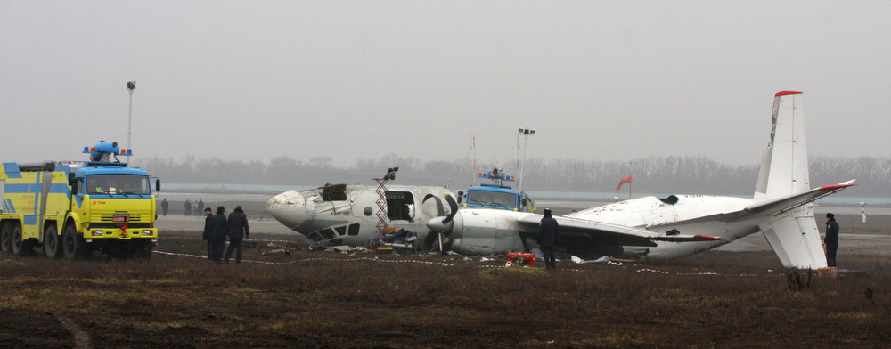 Description of . Ukrainian AN-24 plane is seen after a crash outside an airport  in the eastern Ukrainian city of Donetsk, Thursday, Feb. 14, 2013. A passenger plane carrying soccer fans headed for a match between Ukraine's Shakhtar and Borussia Dortmund, skidded past the landing strip and overturned on Wednesday, killing five people. The plane was carrying 44 people from the Black Sea port of Odessa. (AP Photo/Irina Gorbaseva)