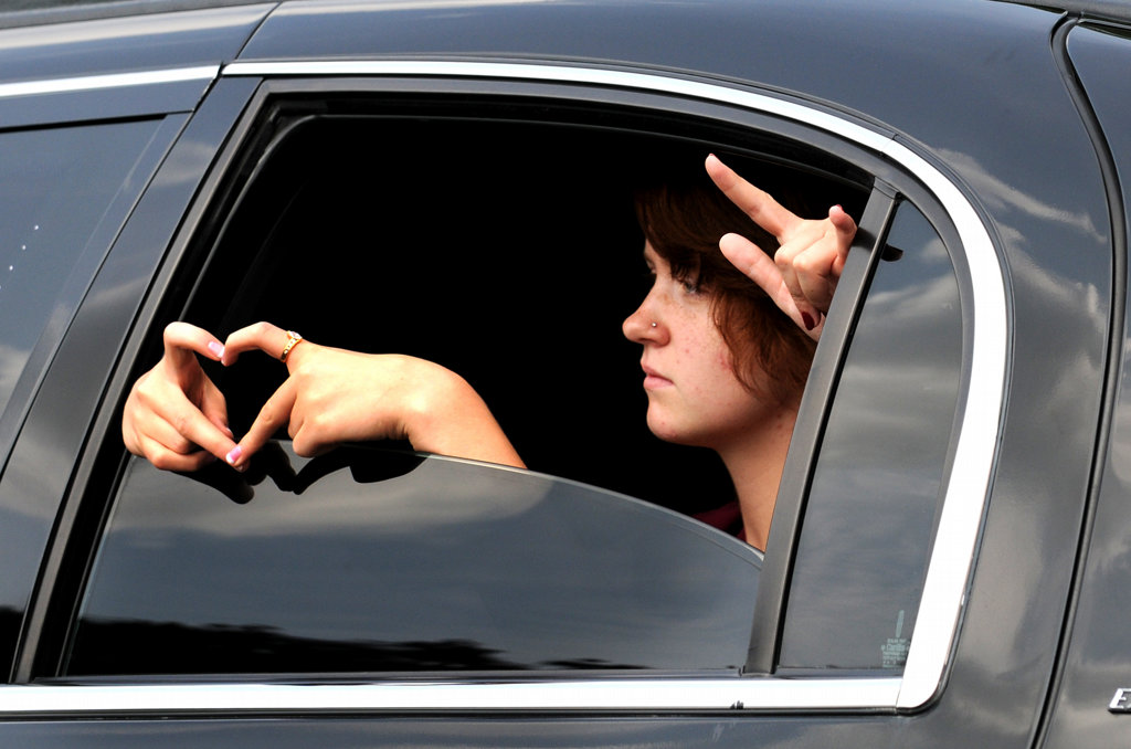 . Officer Scott Patrick\'s daughters, Erin, left, and Amy, not seen, show love signs as they ride in their father\'s funeral procession at Acacia Park Cemetery in Mendota Heights Wednesday.  (Pioneer Press: Jean Pieri)