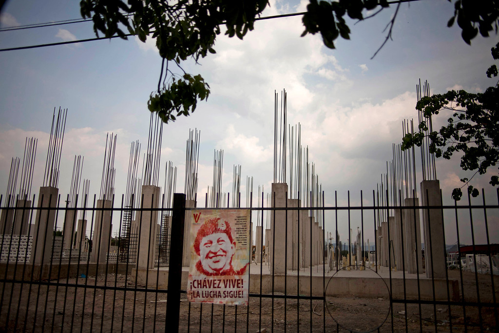 ". In this April 8, 2013 photo, an image of Venezuela\'s late President Hugo Chavez is posted on an iron fence next to a government construction project of would be homes in Valencia, Venezuela. Outside Venezuela\'s capital, power outages, food shortages and unfinished projects abound; important factors heading into Sunday\'s election to replace socialist Chavez, who died last month after a long battle with cancer. An estimated 2 million of Venezuela\'s country\'s nearly 30 million people lack permanent homes, and one of Chavez\'s anti-poverty ""missions\"" builds them. But it\'s been slow going. The government says it has built 370,500 homes and apartments over the past two years, and more than 3 million people applied for them. (AP Photo/Ramon Espinosa)"