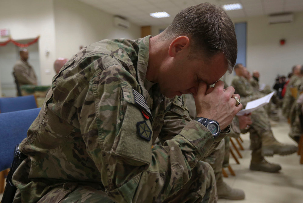 . A U.S. soldier from the Nato-led International Security Assistance Force (ISAF) prays during Christmas Eve celebrations in Kabul, December 24, 2012.  REUTERS/Omar Sobhani