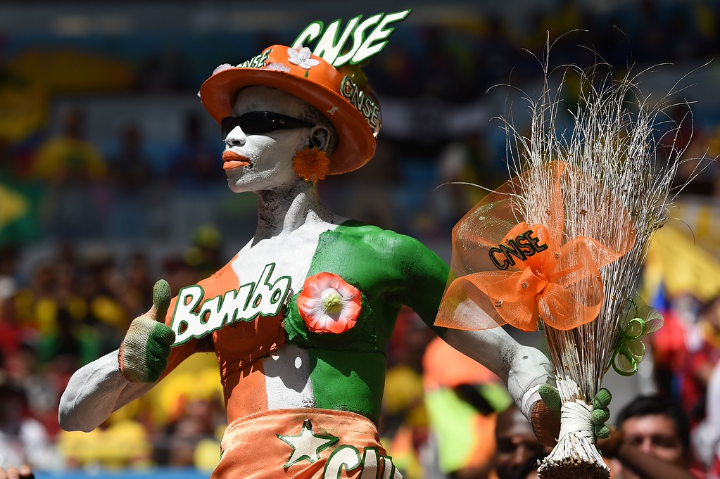 . An Ivorian fan cheers for his team before the start of the Group C football match between Colombia and Ivory Coast at the Mane Garrincha National Stadium in Brasilia during the 2014 FIFA World Cup on June 19, 2014.  AFP PHOTO / PEDRO  UGARTE/AFP/Getty Images