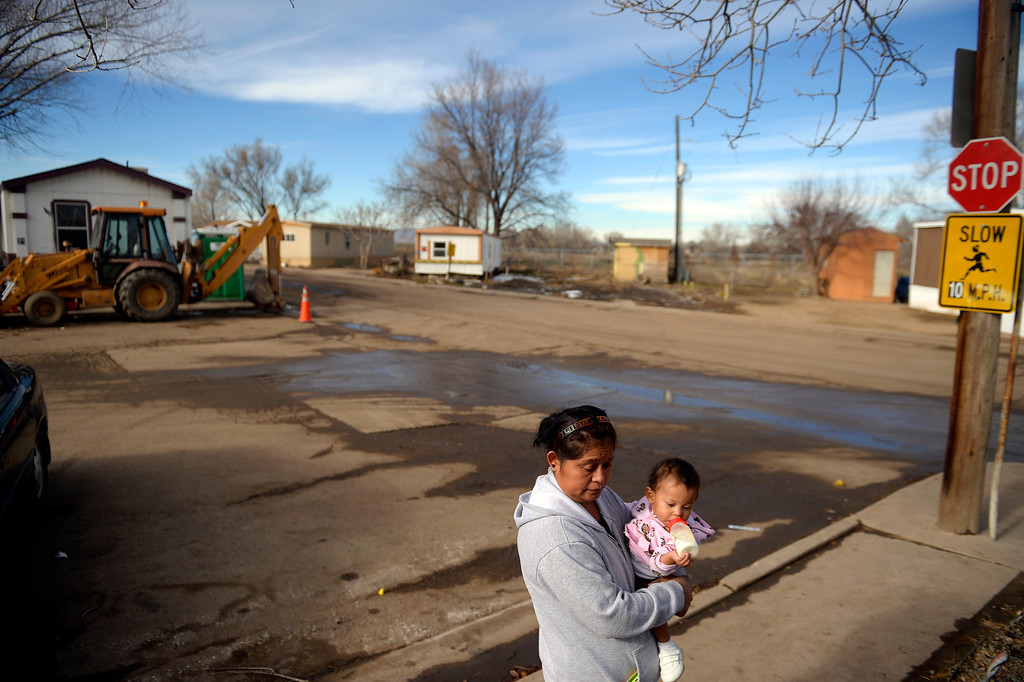 . MILLIKEN, CO - DECEMBER 18: Celerina Luciano holds her daughter at the Evergreen Mobile Home Park. Luciano\'s three-bedroom home, which housed more than a dozen people, was among those totaled by recent flooding. Residents of the mobile home park say that the city of Milliken has not done enough to assist in the rebuilding of the 33-unit residential sub division that was struck hard by recent floods that ravaged much of northern Colorado. (Photo by AAron Ontiveroz/The Denver Post)