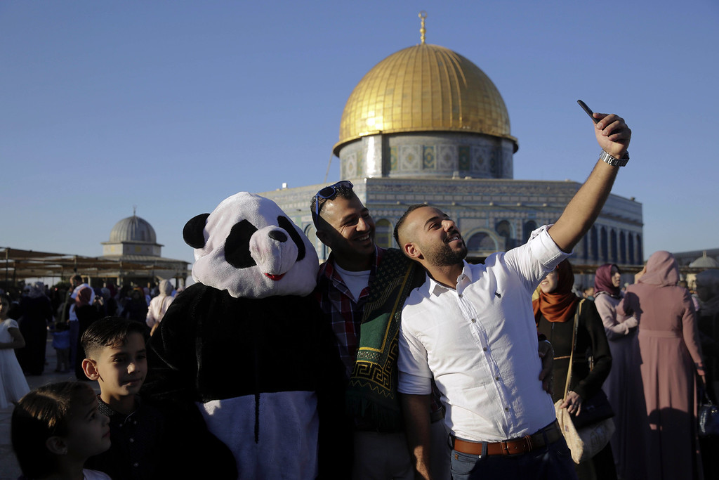 . Palestinians make a selfie in front of the Dome of the Rock shrine in Jerusalem, Friday, June 15, 2018 during the traditional morning prayer of the Muslim holiday of Eid al-Fitr. (AP Photo/Mahmoud Illean)