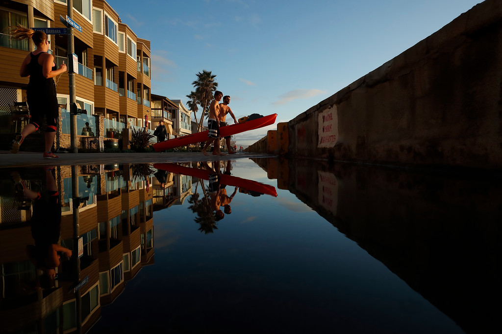 . Two men carry a kayak over standing rainwater on a boardwalk along Mission Beach Tuesday, Feb. 7, 2017, in San Diego. After morning rains, blue skies returned to much of Southern California Tuesday afternoon, as the region awaits a second storm later in the week. (AP Photo/Gregory Bull)