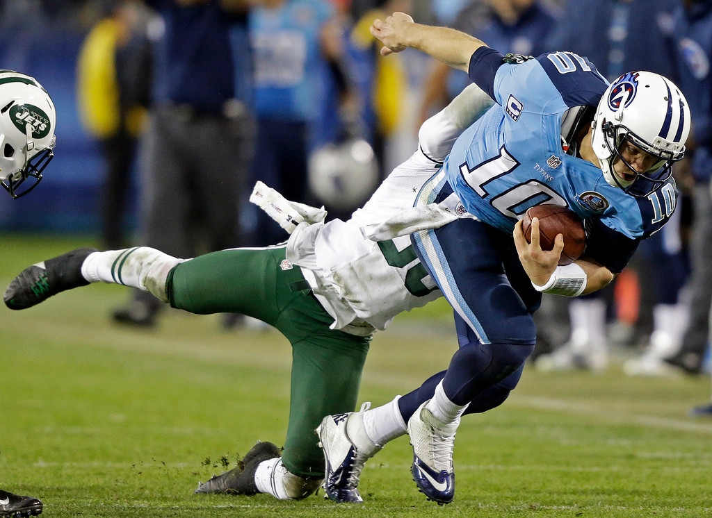 . Tennessee Titans quarterback Jake Locker (10) is tackled by New York Jets free safety LaRon Landry (30) in the third quarter of an NFL football game, Monday, Dec. 17, 2012, in Nashville, Tenn. (AP Photo/Wade Payne)