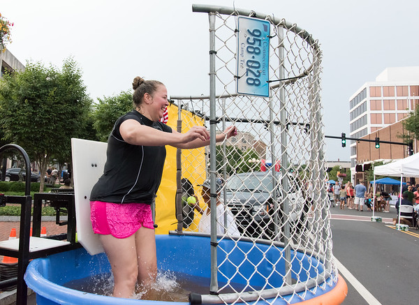 08/07/18 Wesley Bunnell | Staff New Britain Police held their annual National Night Out 2018 on Tuesday evening in a blocked off Central Park area. A player presses the target after failing to hit it with a softball causing New Britain CSO Julie Swan fall into the dunk tank.