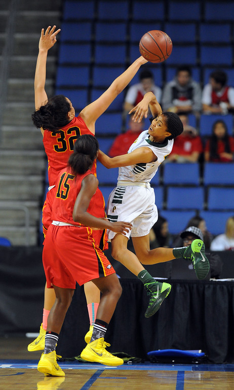 . Under pressure, Poly\'s Arica Carter passes the ball off at Citizens Business Bank Arena in Ontario, CA on Saturday, March 22, 2014. Long Beach Poly vs Etiwanda in the CIF girls open division regional final. 2nd half, Poly won 56-46. Photo by Scott Varley, Daily Breeze)