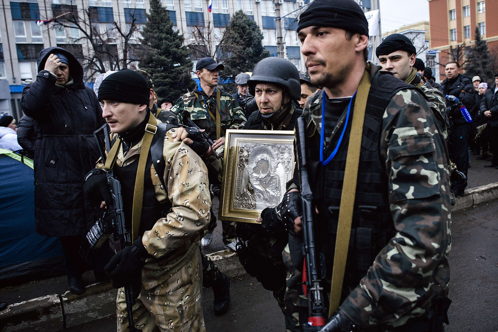 . A woman crosses herself as she watches armed pro-Russian supporters carrying an Eastern Orthodox icon of Mary Magdalene outside the secret service building in the eastern Ukrainian city of Lugansk on April 13, 2014. Ukraine\'s interior minister said on April 13 that both sides had suffered casualties during a raid launched by Ukrainian special forces on a police station in the eastern city of Slavyansk that was seized by pro-Russian gunmen.    AFP PHOTO / DIMITAR DILKOFF