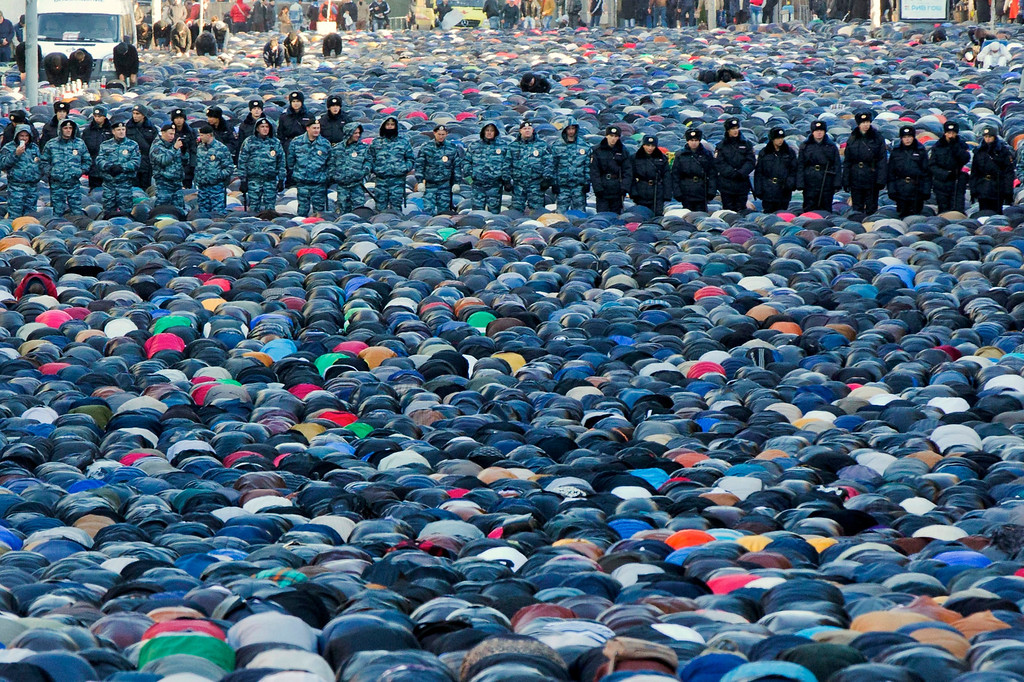 . Russian police officers stand guard as Muslims pray outside the main Moscow mosque during celebrations of Eid al-Adha, a feast celebrated by Muslims worldwide, which Muslims in Russia call Kurban-Bairam in Moscow, Russia, Tuesday, Oct. 15, 2013. According to the press service of Moscowís main police department, about four thousand police officers, Interior troops and others will be ensuring security during the Eid al-Adha celebration events. (AP Photo/Evgeny Feldman)