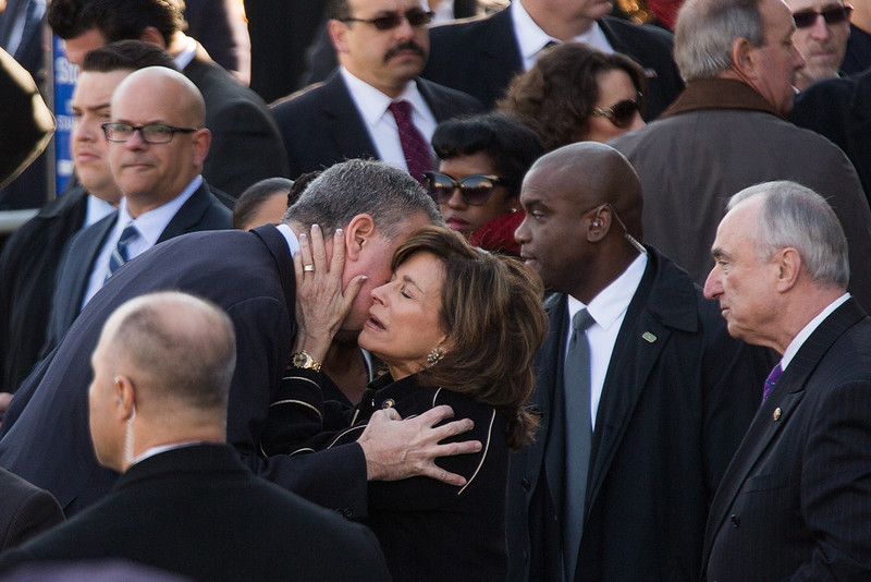 . New York Mayor Bill de Blasio embraces the police commissioner\'s wife Rikki Klieman outside the funeral of slain New York Police Department (NYPD) officer Rafael Ramos at the Christ Tabernacle Church on December 27, 2014 in the Glenwood section of the Queens borough of New York City. Ramos was shot, along with Police Officer Wenjian Liu while sitting in their patrol car in an ambush attack in Brooklyn on December 20. Thousands of fellow officers, family, friends and Vice President Joseph Biden arrived at the church for the funeral.  (Photo by Kevin Hagen/Getty Images)