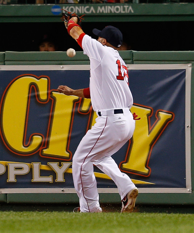 . Shane Victorino #18 of the Boston Red Sox misplays a ball hit buy Jonathan Herrera #18 of the Colorado Rockies in the 7th inning  at Fenway Park on June 25, 2013 in Boston, Massachusetts.  (Photo by Jim Rogash/Getty Images)