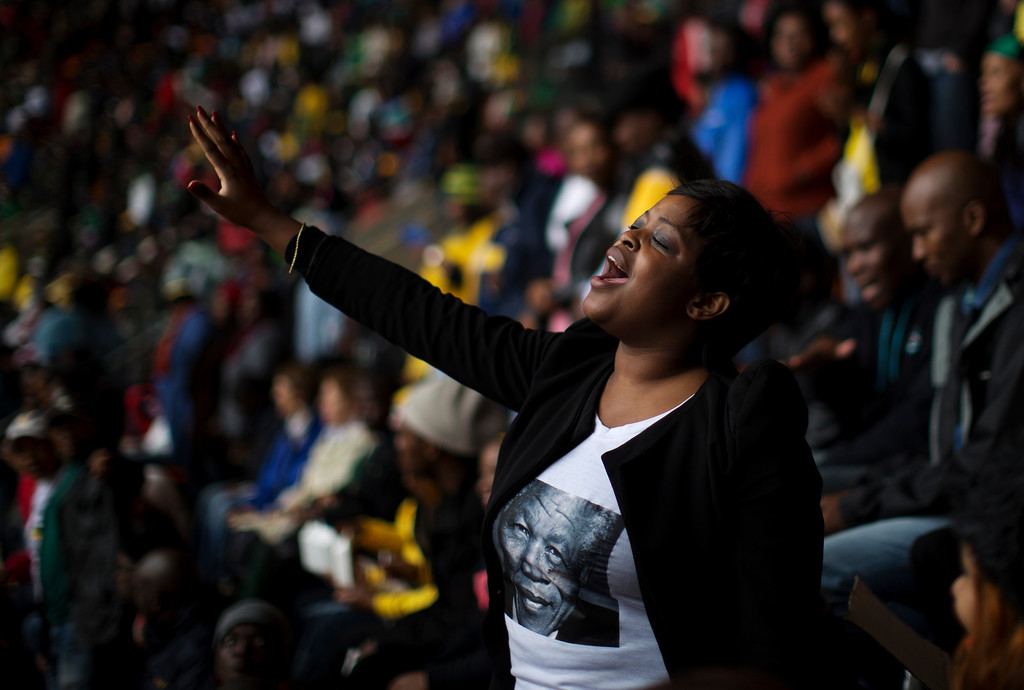 . A woman sings as mourners wait for the memorial service for former South African president Nelson Mandela at the FNB Stadium in Soweto near Johannesburg, Tuesday, Dec. 10, 2013. (AP Photo/Muhammed Muheisen)