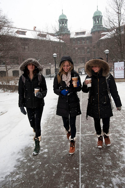 Students walk on the University of Michigan campus past West Hall with their boots, tights, coats and coffees during the winter of 2013 / 2014.  The snowfall record for the area was broken.