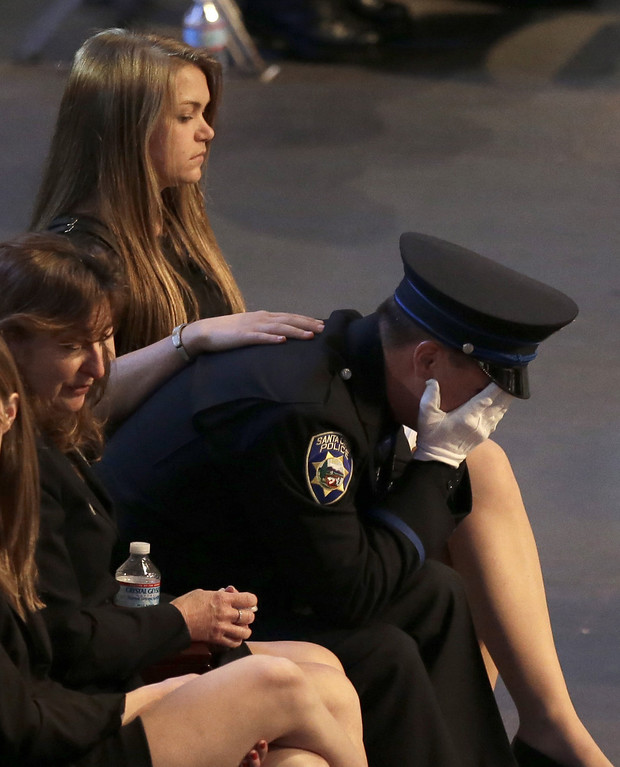 ". Santa Cruz police officer Adam Baker weeps during a memorial service for his father, Sgt. Loran ""Butch\"" Baker, Thursday, March 7, 2013, at HP Pavilion in San Jose, Calif. Sgt. Baker and detective Elizabeth Butler were shot to death on Feb. 27, after arriving at the home of Jeremy Peter Goulet to question him about a misdemeanor sexual assault. (AP Photo/Ben Margot)"