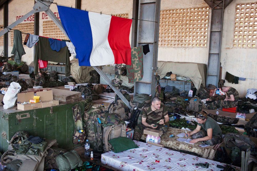 Description of . French soldiers talk under a French flag in a hangar at the Malian army air base in Bamako January 14, 2013. France, which has poured hundreds of troops into the capital Bamako in recent days, carried out more air raids on Monday in the vast desert area seized last year by an Islamist alliance grouping al Qaeda\'s north African wing AQIM alongside Mali\'s home-grown MUJWA and Ansar Dine militant groups. REUTERS/Joe Penney