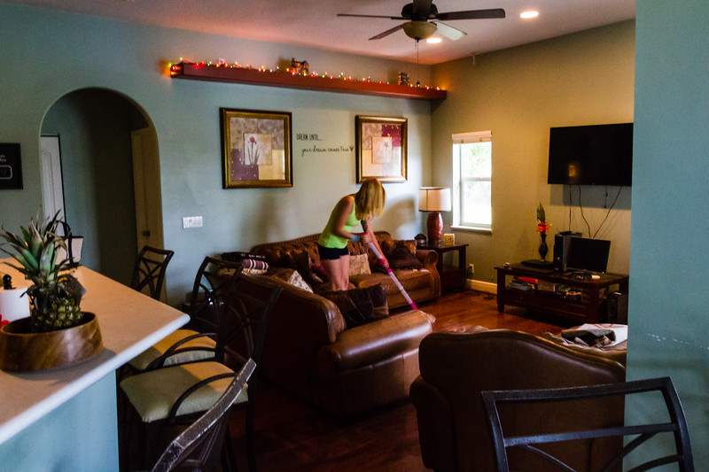"""Shelby Sparrow, 21, of Plantation, Florida, mops the hardwood floor in the loving room  at the All About Recovery younger women's sober home in Loxahatchee, Florida on Friday, June 24, 2016. Residents are required to keep the sober home clean, but once a week, the residents  are assigned an area of the sober house to """"deep clean"""". (Joseph Forzano / The Palm Beach Post)"""