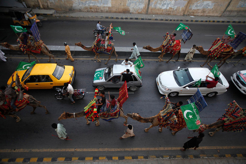 . Supporters of political party Pakistan Muslim League-Functional (PML-F) ride on camels and in vehicles during an election campaign rally in Karachi on May 4, 2013. Pakistan\'s general election will be held on May 11.   REUTERS/Athar Hussain