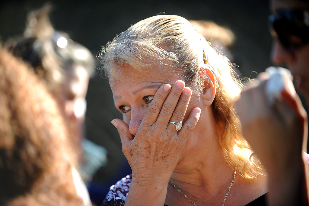 . Luisa Gomez wipes away a tear while visiting the site where her sister was killed at Santa Monica College Monday, June 10, 2013.  Margarita Gomez was one of five people killed in a shooting Friday in Santa Monica, CA.  Mourners gathered for a vigil Monday evening.(Andy Holzman/Los Angeles Daily News)