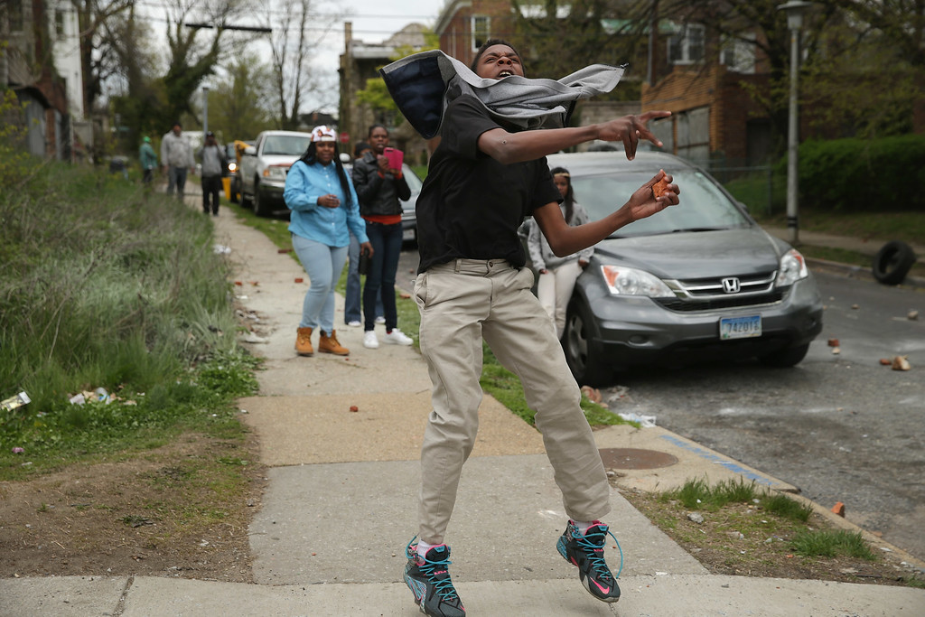 . BALTIMORE, MD - APRIL 27:  Young person hurls a rock at Baltimore Police officers outside the Mondawmin Mall following the funeral of Freddie Gray April 27, 2015 in Baltimore, Maryland. Gray, 25, who was arrested for possessing a switch blade knife April 12 outside the Gilmor Homes housing project on Baltimore\'s west side. According to his attorney, Gray died a week later in the hospital from a severe spinal cord injury he received while in police custody.  (Photo by Chip Somodevilla/Getty Images)